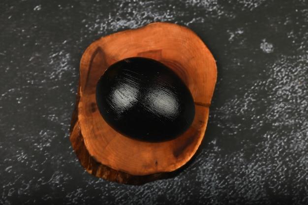 木の板に黒い卵。フラット横たわっていた。ブラックイースター。 3つの黒い卵