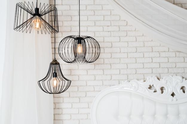 明るい寝室のインテリアの黒いランプ。ぶら下がっている3つのモダンな黒ランプ