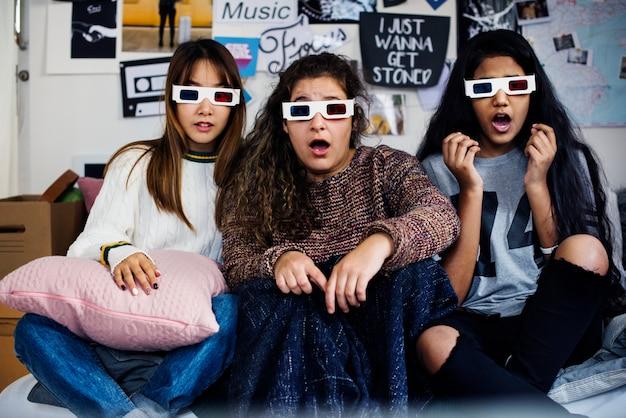 3d映画の眼鏡をかけている10代の少女がびっくりしてテレビを見て驚いた