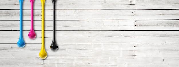 白い木製の背景に分離された3dcmykインクドロップ。横長のバナー。図