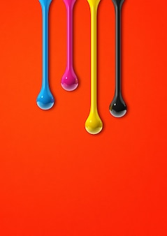 3d cmyk ink drops isolated on red paper background. illustration Premium Photo