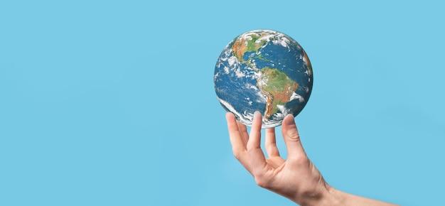 Глобус планеты земли 3d в руке человека, женщине, руках на голубой предпосылке.