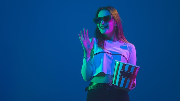 3d eyewear and popcorn. caucasian young woman's portrait isolated on blue studio background in neon light. beautiful model. concept of human emotions, facial expression, sales, ad, cinema, youth.