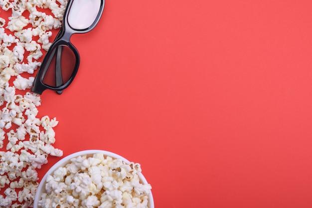3d-очки и попкорн на красном фоне. вид сверху.