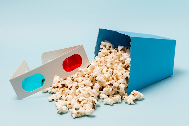 3d glasses near the spilled popcorn from the box on blue backdrop
