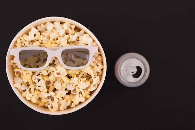 3d glasses, a paper cup of popcorn and a drink in a metal jar are isolated on a black background.