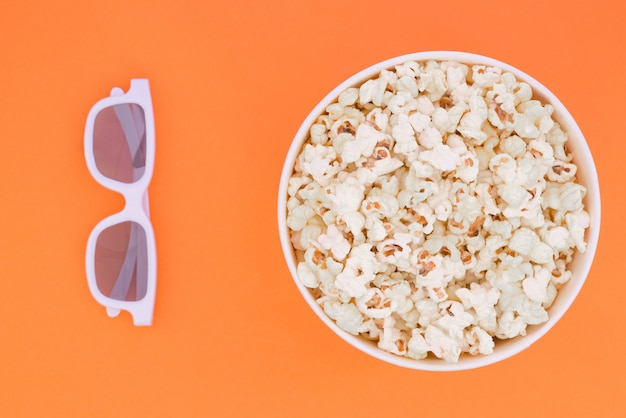 3d glasses and a paper cup with popcorn are isolated on a orange background, a view from above.