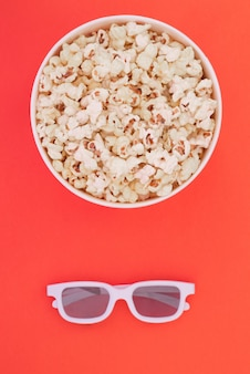 3d glasses and a paper cup with popcorn are isolated on a red background, a view from above