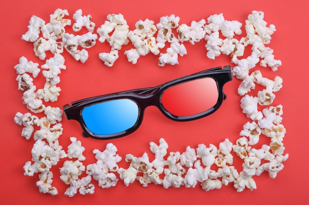 3d glasses in popcorn frame on a red background. close up. top view