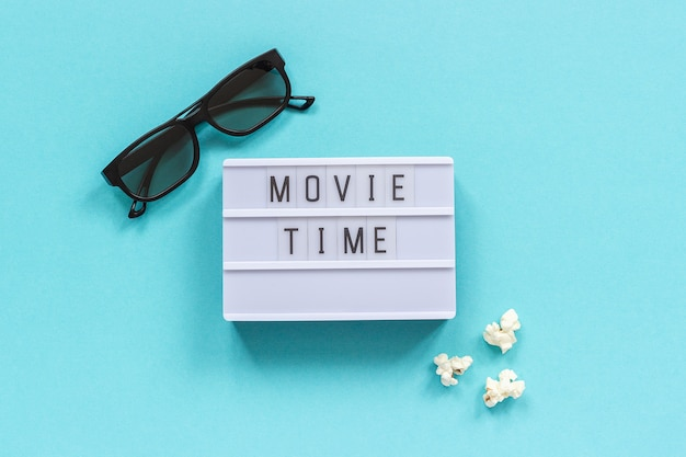 3d glasses, popcorn and lightbox text movie time on blue paper background.