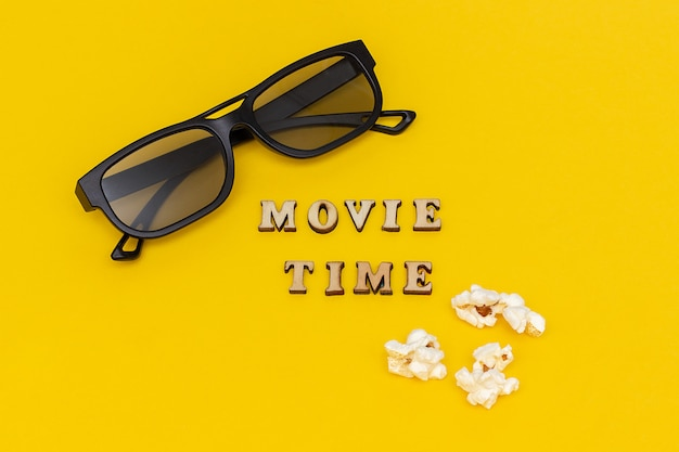 3d glasses, popcorn and text movie time on yellow paper background.
