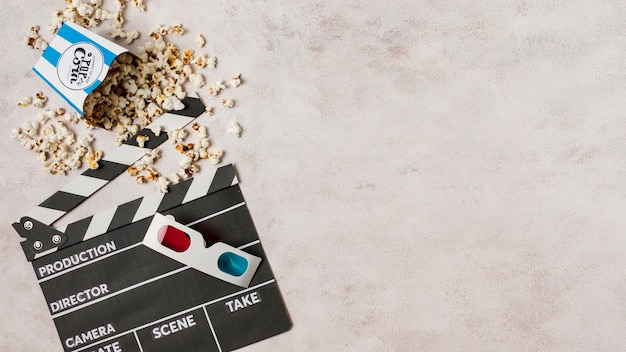 3d glasses with popcorns and clapperboard on concrete backdrop