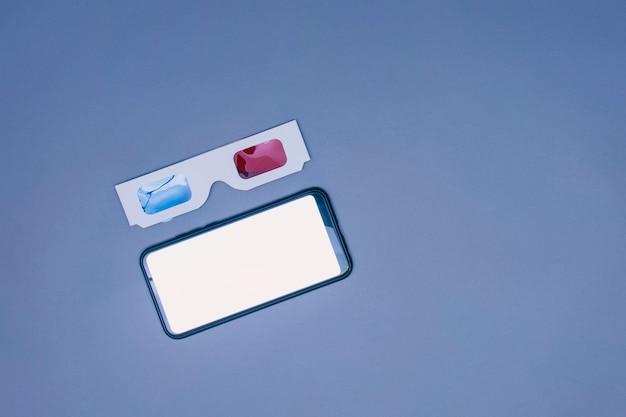 灰色の背景に白い画面でスマートフォンのモックアップと3dメガネ。 3dでビデオを見るためのメガネ。