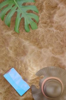 3d 그림입니다. 해변 모래 배경입니다. 밀짚 모자, 열대 잎과 모래 배경에 휴대 전화, 상위 뷰