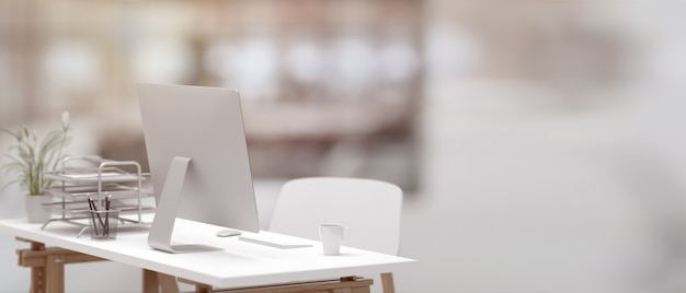 3d illustration, side view of office desk with computer, cup and office supplies in blurred office background, 3d rendering