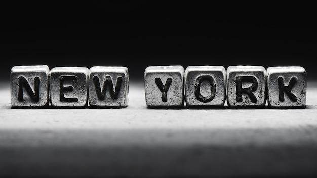 黒灰色の背景のクローズアップの金属の立方体に分離された3d碑文ニューヨーク
