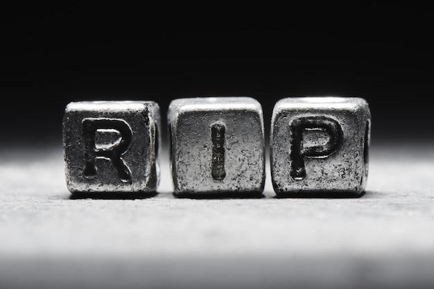 3d надпись rip на металлических кубиках на черном сером фоне крупным планом изолированы