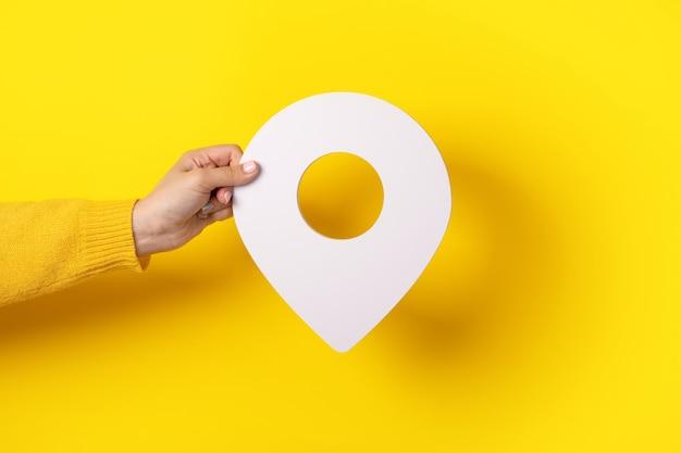 노란색 배경 위에 손에 3d 위치 기호