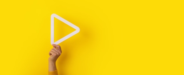 3d media play button in hand over yellow background, panoramic layout