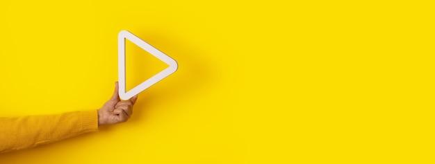 黄色の背景、パノラマレイアウトの上に手に3dメディア再生ボタン