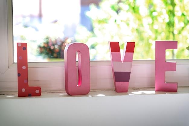 後ろに庭がある窓の前に3dピンクの文字。愛とバレンタインデー。家での幸せ