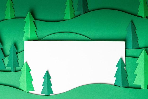 緑の壁に3dポップアウトクリスマスツリーの紙のアートワーク。クリスマスツリー切り絵デザインカード。上面図。フラットレイ