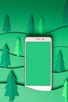 緑の壁にスマートフォンでクリスマスツリーの紙のアートワークを3dポップアウトします。コピースペース付きのクリスマスツリー切り絵デザインカード。上面図。フラットレイ