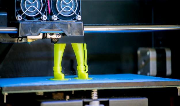 3d 프린터는 녹은 플라스틱 녹색의 형태를 인쇄합니다.