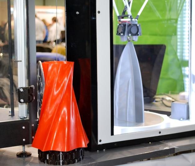 3d 프린터가 작동하고 뜨겁게 녹은 플라스틱 클로즈업에서 물체를 만듭니다. 자동 3차원 3d 프린터는 실험실에서 플라스틱 붉은 색 모델링을 수행합니다.
