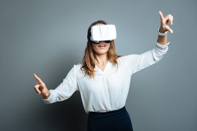 3dリアリティ。 3dメガネをかけ、最新のテクノロジーを使用しながらバーチャルリアリティを探索するポジティブな喜びの素敵な女性