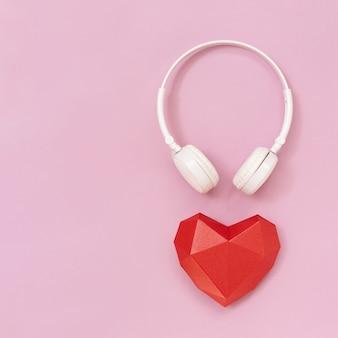 3 d赤い紙のハートと白いヘッドフォン。音楽祭、ラジオ局、音楽愛好家のためのコンセプト。音楽とともに生きる。最小限のスタイル。