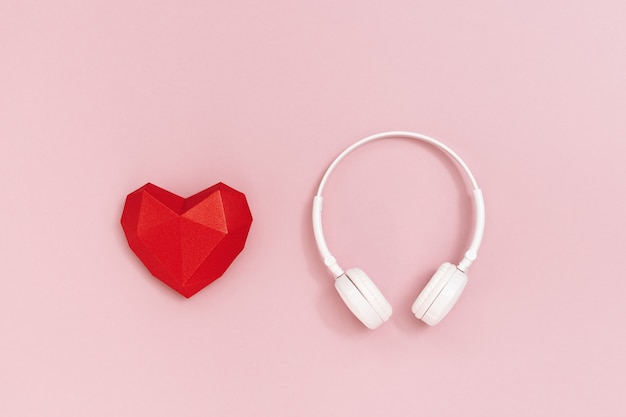 3d red paper heart and white headphones