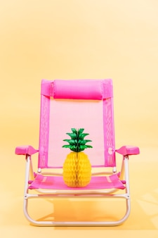 3d render pink beach chair with a paper pinepple on it on yellow background