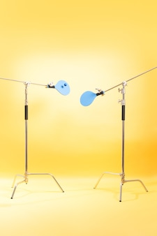 3d render set of blue beach paddles fixed on tripods on a yellow studio background