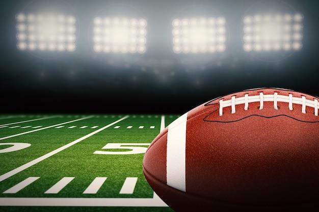 緑のフィールドにアメリカンフットボールのボールを3dレンダリング