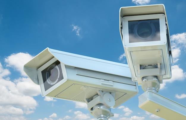 3d-рендеринг камеры видеонаблюдения или камеры безопасности на фоне голубого неба