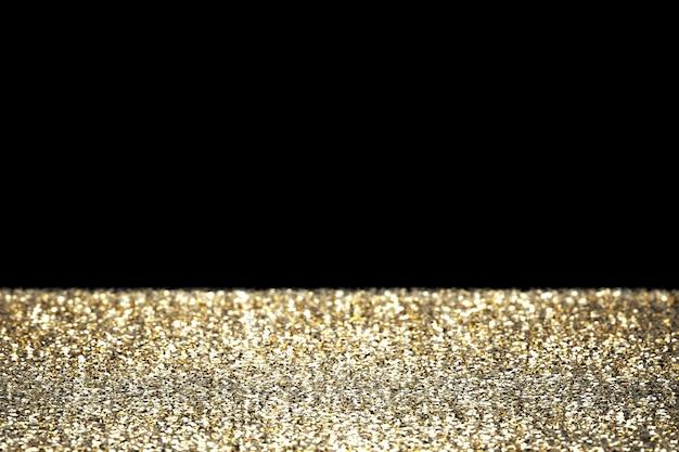 黒の背景にボケ味のある3dレンダリングゴールドラメ