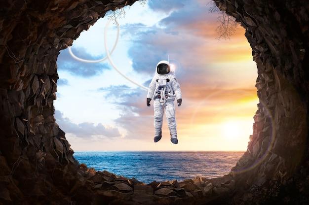 3d 렌더링 행성 지구와 동굴에서 밖을 내다보는 바다 지구 행성에 서 있는 우주 비행사