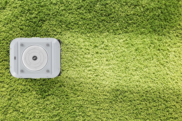 3d-рендеринг робот-пылесос на зеленом ковре сверху