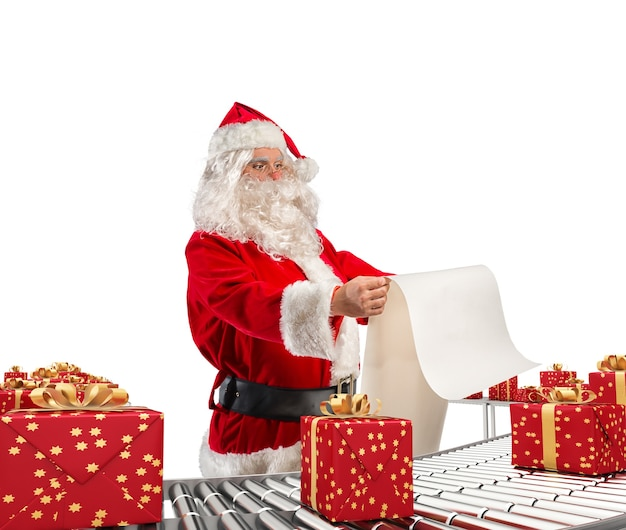 3d-рендеринг санта-клауса, проверяющего список рождественских подарочных коробок и завернутых на конвейерный ролик