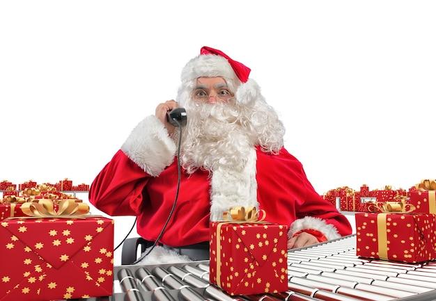 3d 렌더링 산타 클로스는 의자에 앉아 크리스마스 선물 상자를 확인하고 컨베이어 롤러에 싸인 전화를 통해 요청을받습니다.