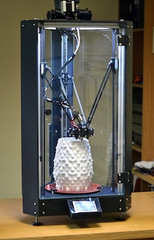 3d 프린터는 흰색 추상 꽃병 형태로 개체를 인쇄합니다.