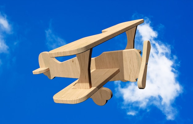 青い空に3d木のおもちゃの飛行機