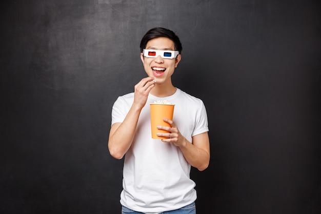 Досуг, фильмы и концепция образа жизни. забавный и заинтересованный азиатский парень в 3d очках улыбается, заинтригованный, как смотрит потрясающий новый фильм, ест попкорн в кино,