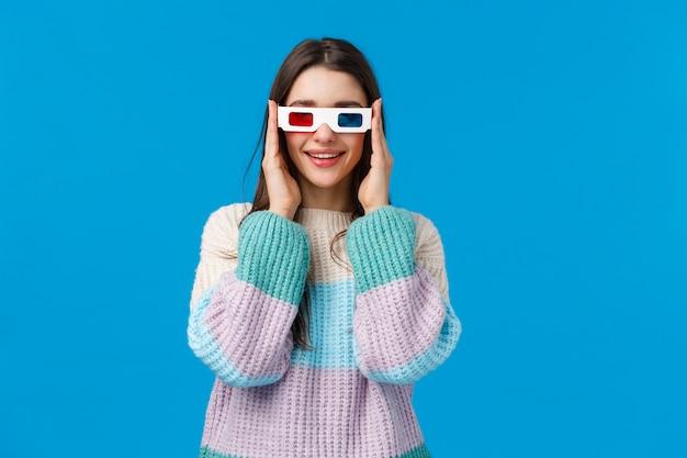 Включите, давайте начнем. привлекательная веселая и счастливая улыбающаяся молодая женщина в зимнем свитере, носит 3d очки и улыбается, соблазняет увидеть новую премьеру в кино, смотрит фильм над синей стеной