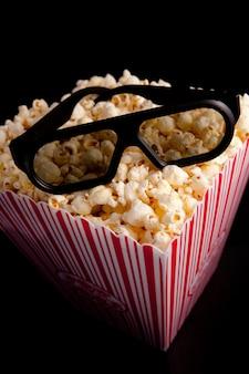 ポップコーンの箱の上に横たわる3d眼鏡