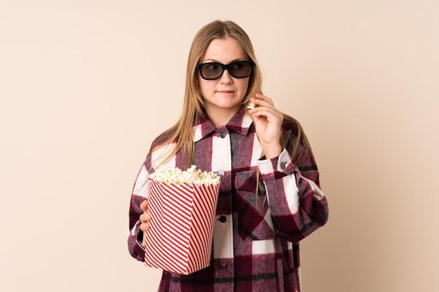 Подросток украинская девушка изолирована на бежевом с 3d-очками и держит большое ведро попкорна