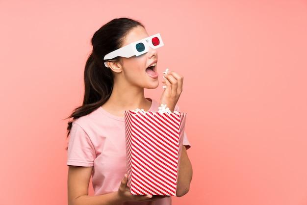 Девочка-подросток над изолированной розовой стеной ест попкорн в 3d-очках