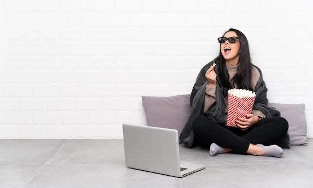 Молодая колумбийская девушка в комнате с 3d-очками и с большим ведром попкорна