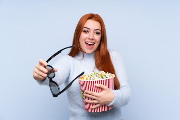 Рыжая девушка-подросток над синим с 3d-очками и с большим ведром попкорна